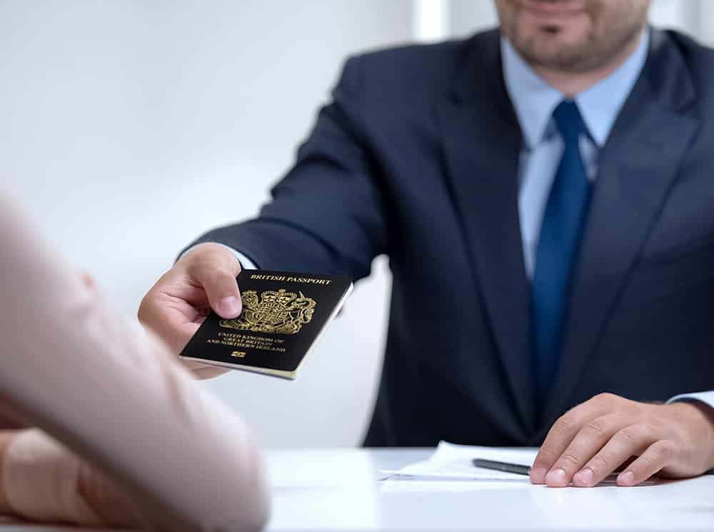 Immigration solicitor handing over uk passport to client
