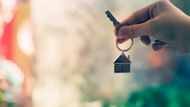woman holding key with house key ring attached