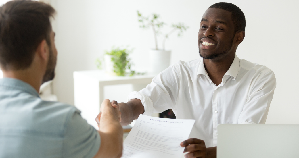 employer shaking hands with employee over settlement agreement