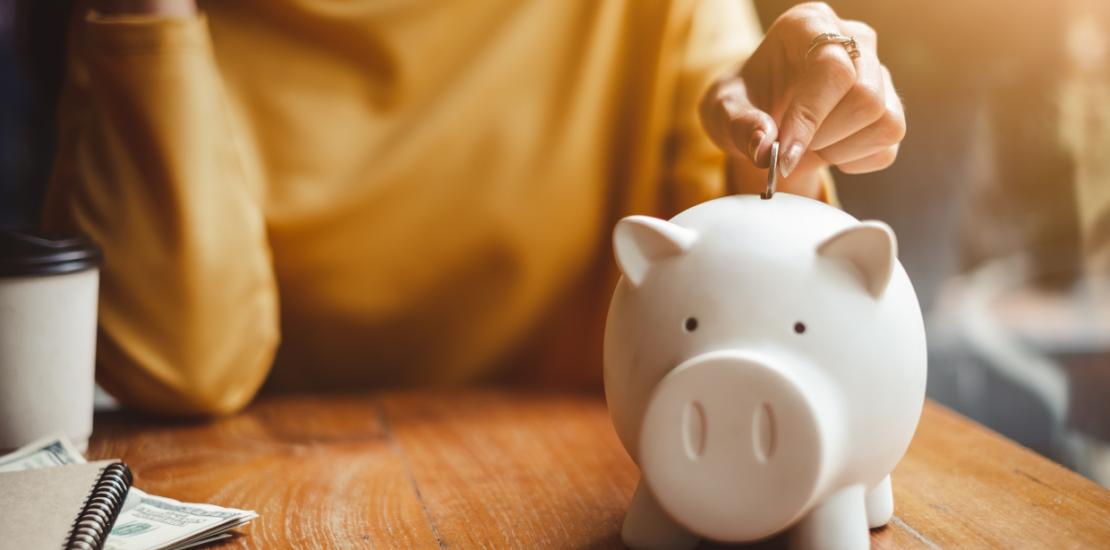 woman putting money into piggy bank