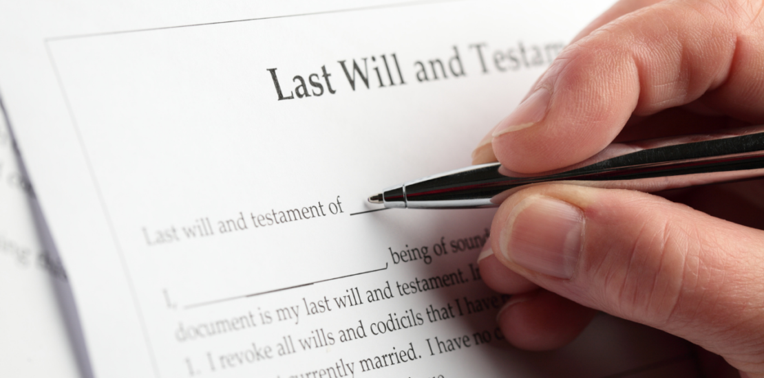 man writing on will and testament document