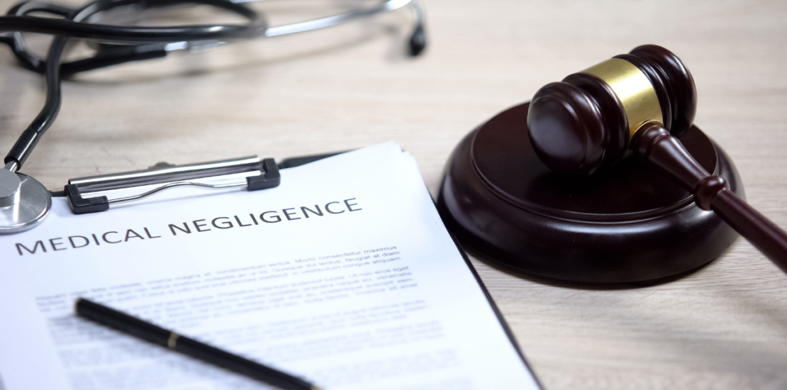 medical negligence documents with judges hammer next to it