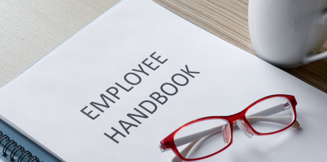 employee handbook with red glasses sitting on top