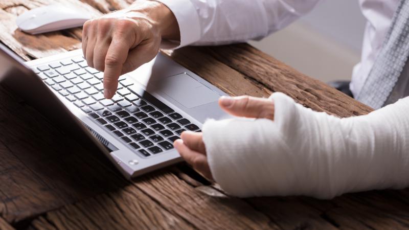 man with injured arm typing on laptop